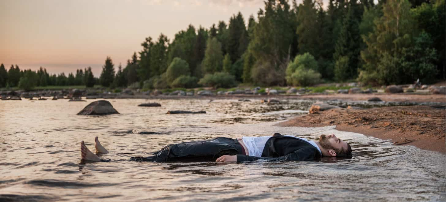 A young man cools off by lying down at the water's edge