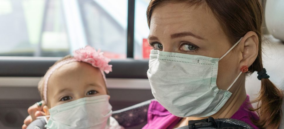 mother and daughter wearing pollution protection masks in taxi