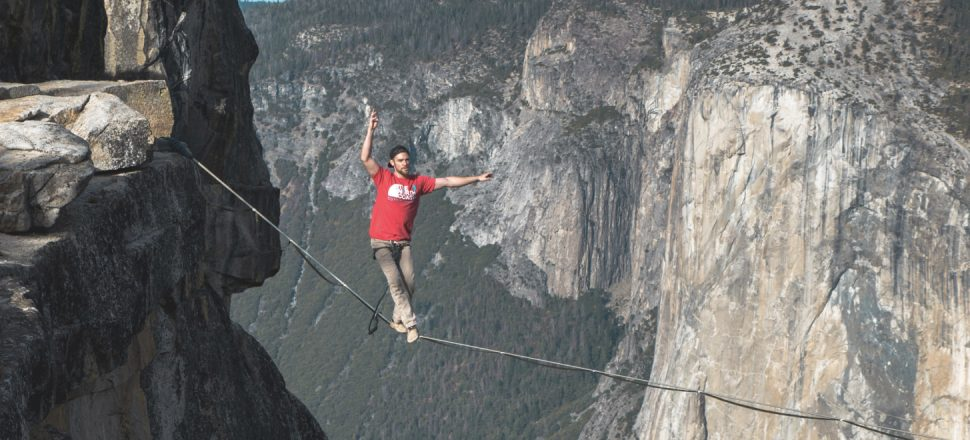 A young man walks a tightrope between the tops of two mountains